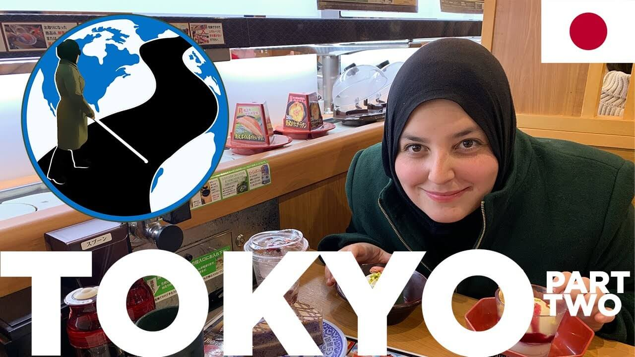 A thumbnail for Traveling Blind in Japan - Planes, Trains and Canes Episode 5 Part 2. It shows Mona smiling over a meal infront of a sushi conveyer belt. Superimposed on the image is the PTC Logo and a flag of Japan.