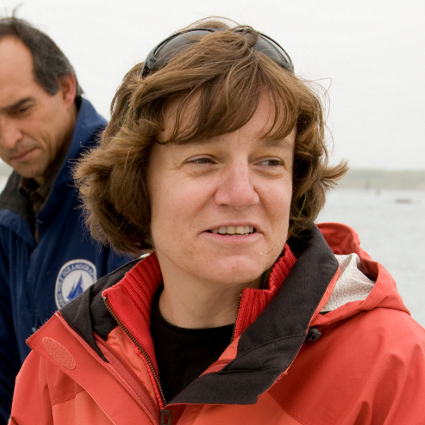 A photo of Dr. Amy Bower posing on camera. Behind her the sky is cloudy and a body of water can be seen. She is wearing a red jacket and has sunglasses on her head.