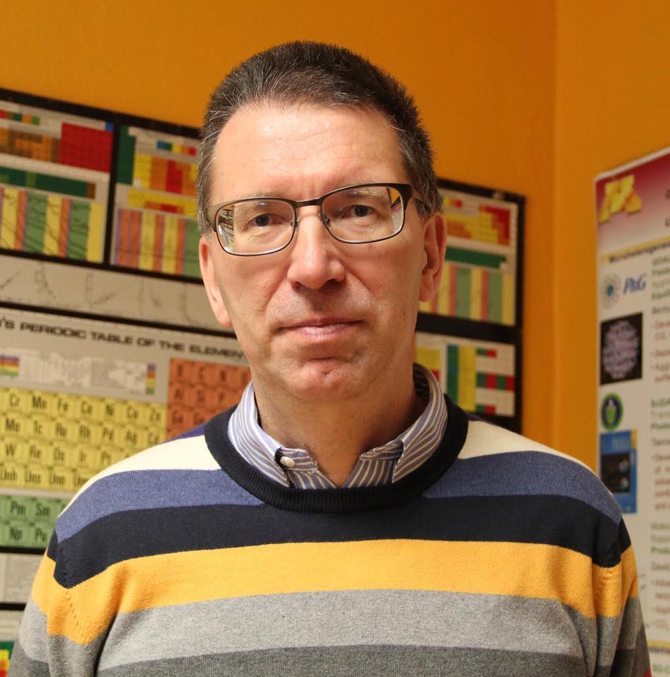 An image of Dr. J. Ilja Siepmann. Dr. Siepmann is wearing a striped sweater over a collared shirt. He wears glasses and is posing for the camera. On the wall behind him is a periodic table and a research poster.