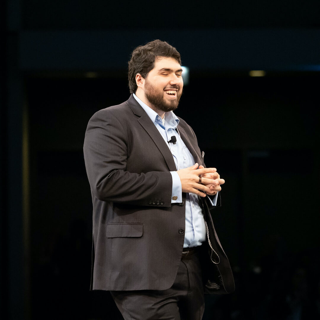 A photo of Sina Bahram giving a presentation on a stage. He is wearing a full suit with a blue shirt. A mic can be seen on his chest. Behind him the background is dark.